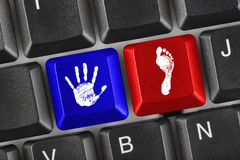 Printout of hand and foot on computer keys. Computer keyboard with printout of hand and foot keys stock images
