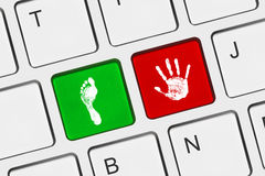 Printout of hand and foot on computer keys Royalty Free Stock Images