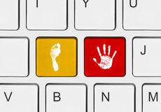 Printout of hand and foot on computer keys Stock Photos