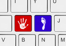 Printout of hand and foot on computer keys Stock Images