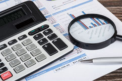 Printout with table and chart, electronic calculator, magnifying. Glass and ballpoint pen on wooden table stock photography