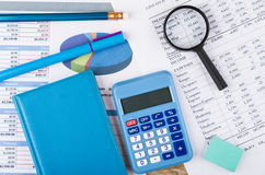 Printouts of financial information, notepad, calculator and magn Stock Image