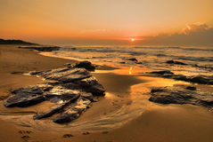 Prints on beach seascape sunrise. This is a typical South African sunrise, taken in Kwazulu natal. The receding tide left the rocks wet, highlighting their Stock Photography