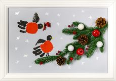 Prints of the hands palms are stylized as bullfinches. Branch of fir tree with cones, red apples and white balls. Handmade picture. In a frame as an Stock Photo