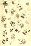 Prints of palms and foots. Over paper texture Stock Images