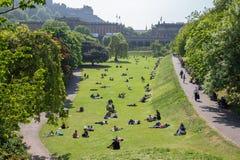 Prinzen Street Gardens mit den Leuten, die im Gras, Edinburgh sitzen lizenzfreies stockfoto