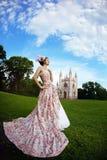 Prinzessin in einem Weinlesekleid vor Schloss stockfotografie