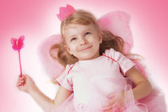 Prinzessinmädchen, das mit rosa Schmetterlingsflügeln liegt Stockfotografie