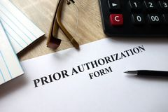 Prior authorization form. With pen, calculator and glasses on desk royalty free stock image