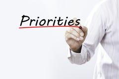 Prioridades da escrita da mão do homem de negócios com marcador, concep do negócio Imagens de Stock Royalty Free
