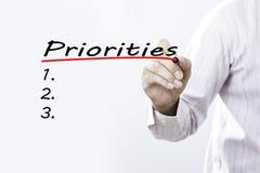 Prioridades da escrita da mão do homem de negócios com o marcador vermelho no transpare Fotografia de Stock