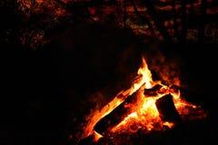 Priorità alta del fuoco di accampamento sotto un cielo notturno rosso Immagine Stock