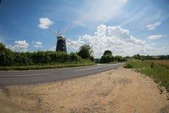 Priorità alta della strada del fondo del cielo blu della linea costiera della Norfolk con un mulino a vento nel mezzo Fotografia Stock Libera da Diritti