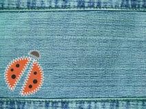 Priorità bassa dei jeans con il ladybug Fotografia Stock Libera da Diritti