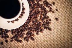 Priorità bassa del caffè con una tazza & i semi di cacao torrefatti Immagini Stock