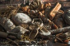 Priorità bassa del pane Brown ed intere pagnotte bianche del grano avvolti in composizione nella carta kraft su legno scuro rusti immagini stock