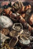 Priorità bassa del pane Brown ed intere pagnotte bianche del grano avvolti in composizione nella carta kraft su legno scuro rusti fotografia stock libera da diritti