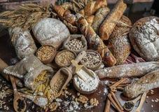 Priorità bassa del pane Brown ed intere pagnotte bianche del grano avvolti in composizione nella carta kraft su legno scuro rusti immagine stock libera da diritti