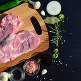Priorità bassa dell'alimento Carne su un tagliere e pepe, foglia di alloro, rosmarino, cipolle, sale himalayano, olio d'oliva, sa Fotografie Stock Libere da Diritti