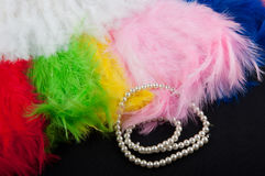 Priorità bassa della decorazione Le belle piume molli di colore e la collana del Perl mettono sul tessuto nero Fotografie Stock