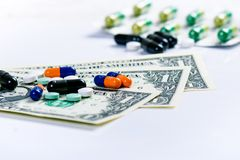 Priorità bassa della farmacia Pillole su una banconota isolata su un fondo bianco Tipi differenti di capsule sulla banconota dei  Immagine Stock Libera da Diritti