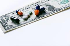 Priorità bassa della farmacia Pillole su una banconota isolata su un fondo bianco Tipi differenti di capsule sulla banconota dei  Immagini Stock