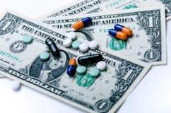 Priorità bassa della farmacia Pillole su una banconota isolata su un fondo bianco Tipi differenti di capsule sulla banconota dei  Fotografia Stock Libera da Diritti