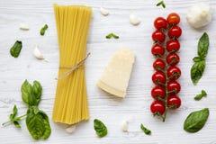 Priorità bassa della pasta Ingredienti per la cottura della pasta su una tavola di legno bianca Disposizione piana Fotografia Stock
