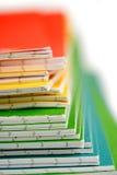 Priorità bassa della pila dei taccuini di colore Fotografie Stock Libere da Diritti