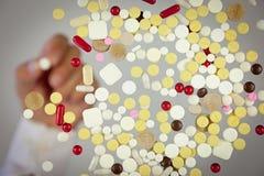 Priorità bassa delle pillole e mano che tiene una pillola Fotografia Stock