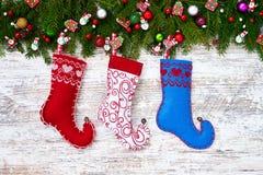 Priorità bassa di natale Albero di abete di Natale con i calzini di Natale sul fondo bianco del bordo di legno Fotografie Stock