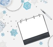 Priorità bassa di natale con il posto per testo Fiocchi di neve blu, perle brillanti, taccuino e penna su fondo bianco Piano per  Immagini Stock