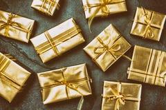 Priorità bassa di natale Contenitori di regalo dorati sul fondo dell'ardesia Disposizione piana, vista superiore Fotografie Stock Libere da Diritti