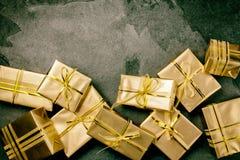 Priorità bassa di natale Contenitori di regalo dorati sul fondo dell'ardesia Disposizione piana, vista superiore Fotografia Stock