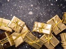 Priorità bassa di natale Contenitori di regalo dorati sul fondo dell'ardesia Disposizione piana, vista superiore Fotografie Stock