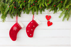 Priorità bassa di natale Cuore e calzini rossi di Natale su fondo di legno bianco, albero di abete di Natale immagini stock libere da diritti