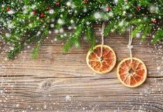 Priorità bassa di natale Ramo ed arancia di albero dell'abete di Natale su vecchio fondo di legno Fotografie Stock Libere da Diritti