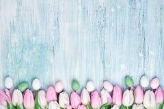 Priorità bassa di Pasqua Le uova di Pasqua decorative ed i tulipani rosa rasentano il fondo di legno Carta di festa, spazio della Fotografie Stock