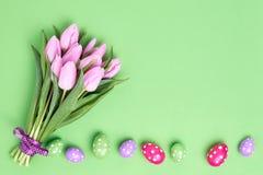 Priorità bassa di Pasqua Uova di Pasqua decorative e mazzo rosa dei tulipani su fondo verde Copi lo spazio Fotografia Stock
