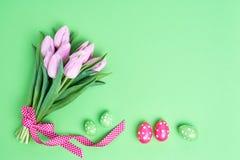 Priorità bassa di Pasqua Uova di Pasqua decorative e tulipani rosa su fondo verde Copi lo spazio Immagine Stock Libera da Diritti