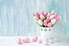 Priorità bassa di Pasqua Uova di Pasqua decorative e tulipani rosa in vaso Fotografie Stock