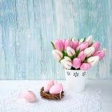Priorità bassa di Pasqua Uova di Pasqua decorative e tulipani rosa in vaso Fotografia Stock
