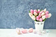 Priorità bassa di Pasqua Uova di Pasqua decorative e tulipani rosa in vaso Immagine Stock
