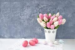 Priorità bassa di Pasqua Uova di Pasqua decorative e tulipani rosa in vaso bianco Fotografie Stock Libere da Diritti