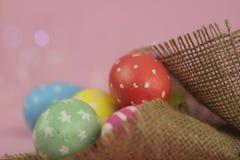 Priorità bassa di Pasqua Uova dipinte verdi, rosse e gialle fatte a mano in tela di sacco su un fondo rosa con bokeh fotografia stock