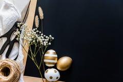 Priorità bassa di Pasqua Uova di Pasqua in vari progettazioni, forbici, fiori e palla dorati della canapa sopra il bordo di stori Fotografia Stock