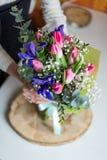 Priorità bassa vaga Mani del fiorista che mostrano mazzo dei fiori della molla Fotografie Stock
