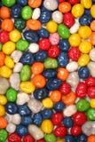 Priorità bassa verticale fatta dei dolci multi-coloured con l'uva passa 1 Fotografia Stock