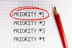 Priorité première identifiée par le cercle rouge sur le carnet de maths images stock