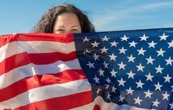 Priorit? bassa del grunge di indipendenza Day Una donna con capelli ricci neri sta tenendo una bandiera americana Il concetto di  immagine stock libera da diritti